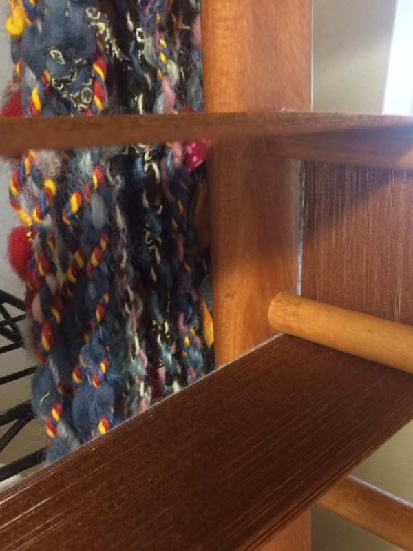 New warp on frame, with handspun  Nomad Caravan  peeking through.