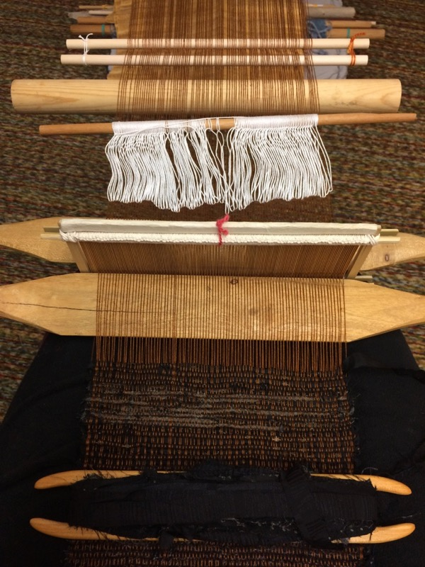 Here's the setup. Don't be confused by the rolled up weaving on the floor beneath (extra sticks at the top of the photo.) This one has lease sticks, a fat shed stick, string heddles, two swords and a reed. I had to beat with the sword rather than the reed to get this packed nicely.