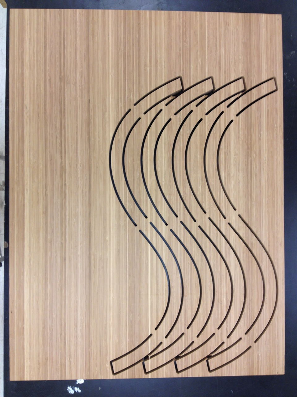 The coffee table's four curves after being cut by a shopbot. Tabs are left in order to prevent the curves from moving during cutting