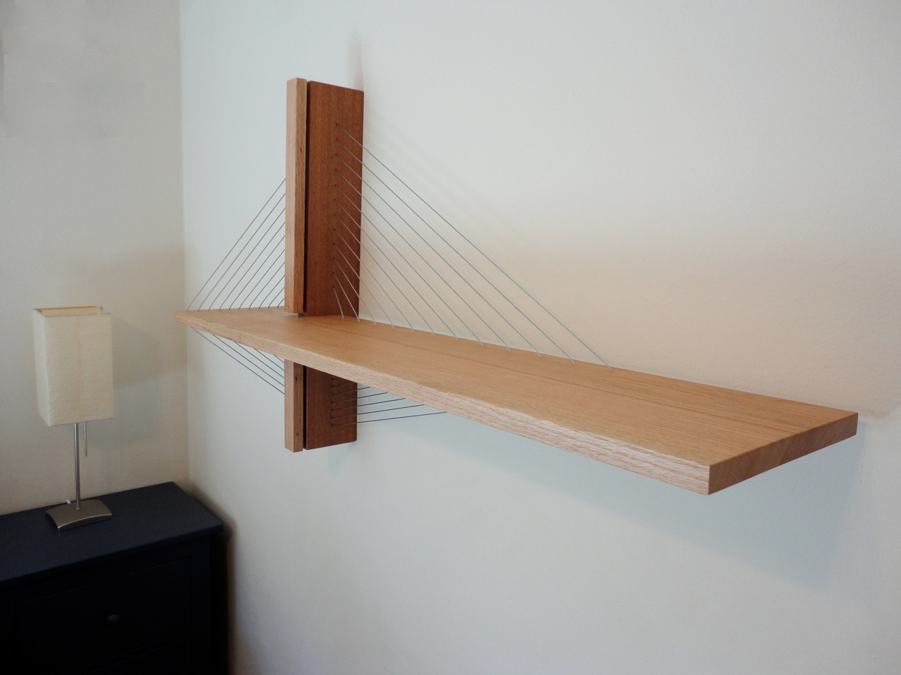 Suspension shelf by robby cuthbert. A modern floating shelf made of wood and steel cable.