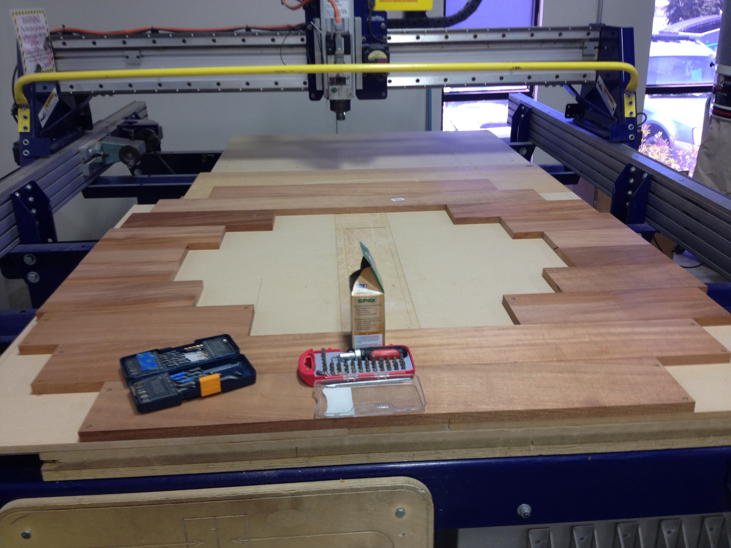 While the final ring may look solid, it is actually made up of 64 individual pieces all glues together in four layers. Here, the mahogany that will comprise the top layer is laid out on the Shopbot table. Before being screwed onto the Shopbot bed, every piece had to be cut to just the right size so that the final layout would accommodate the ring design while avoiding unnecessary waste. Each piece also had to be carefully abutted with its neighbors so there would be no cracks after the final assembly.