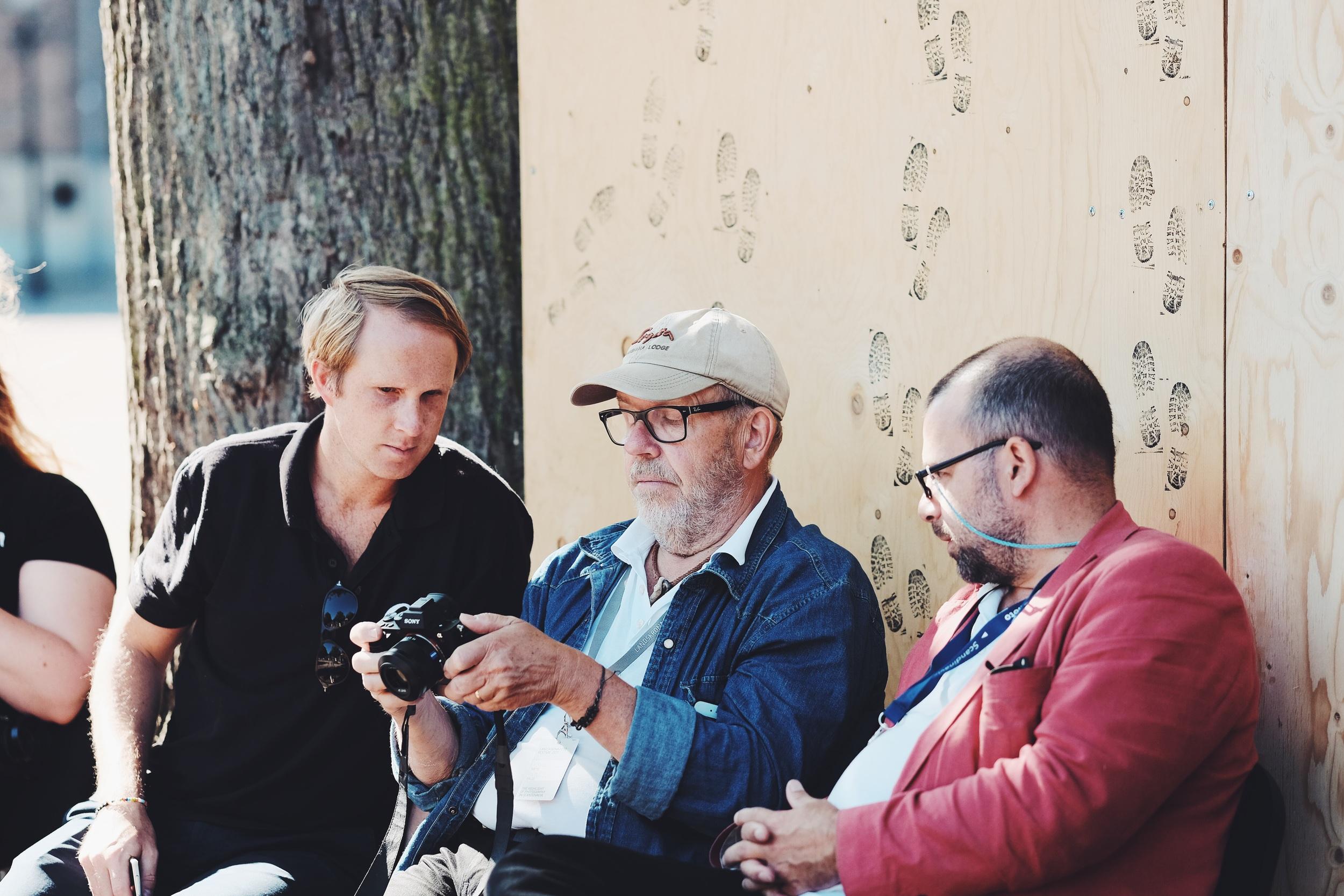 Johan och Anders hjälper en kund med sin kamera.