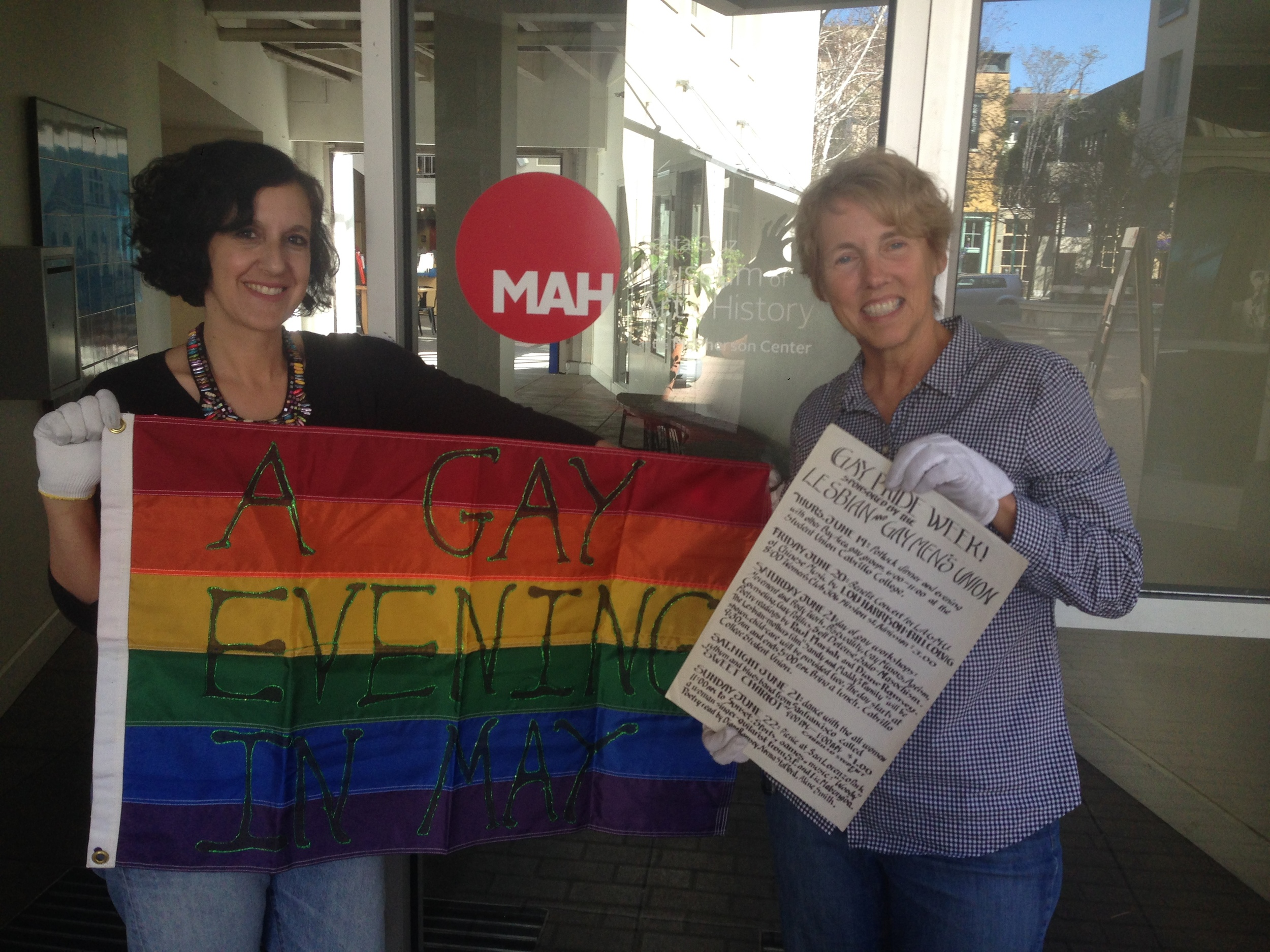 The MAH's Curator of Collections, Marla Novo, holds a flag for A Gay Evening in May (AGEM) in the 1980s and Diversity Center Board member, Pat Dellin, holds an original flyer from the first Santa Cruz Pride in 1975, part of the new LGBTQ archives at the MAH.