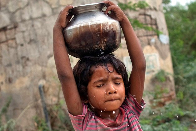 Five-year-old Joshiya carries a  metal pitcher filled with water from a near-by well at Badarganj village  in the western Indian state of Gujarat August 5, 2012. Picture taken  August 5, 2012. To match feature INDIA-DROUGHT/ REUTERS/Ahmad Masood