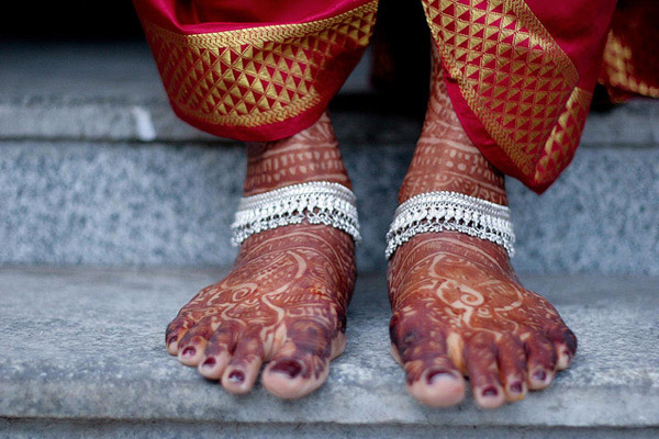 The photograph here shows the feet of a Tamil bride getting ready for  her wedding. The feet of this bride are adorned with a silver anklet and  Mehndi. Mehndi (henna) which is a prominent feature of Indian brides.  (Image source:  Raghuram Ashok )