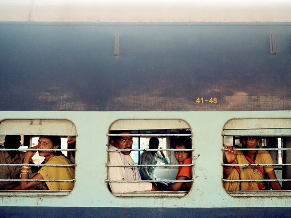 Photograph by Thomas Holton/Getty Image Passengers peer out the windows of a train in a station in Varanasi, a 3,000-year-old holy city