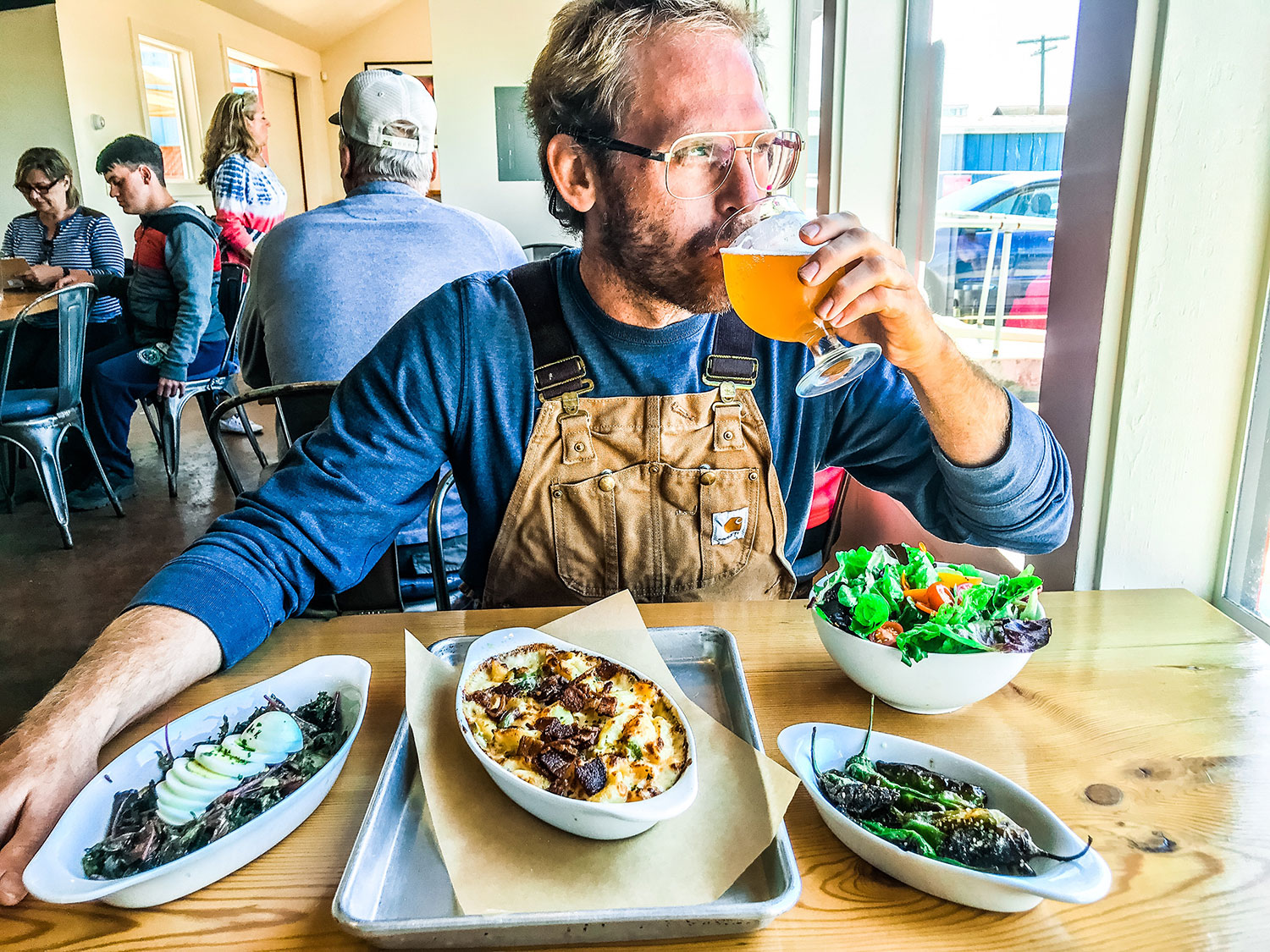 a man sits at Overtime Brewery drinking a beer with an array of dishes in front of him