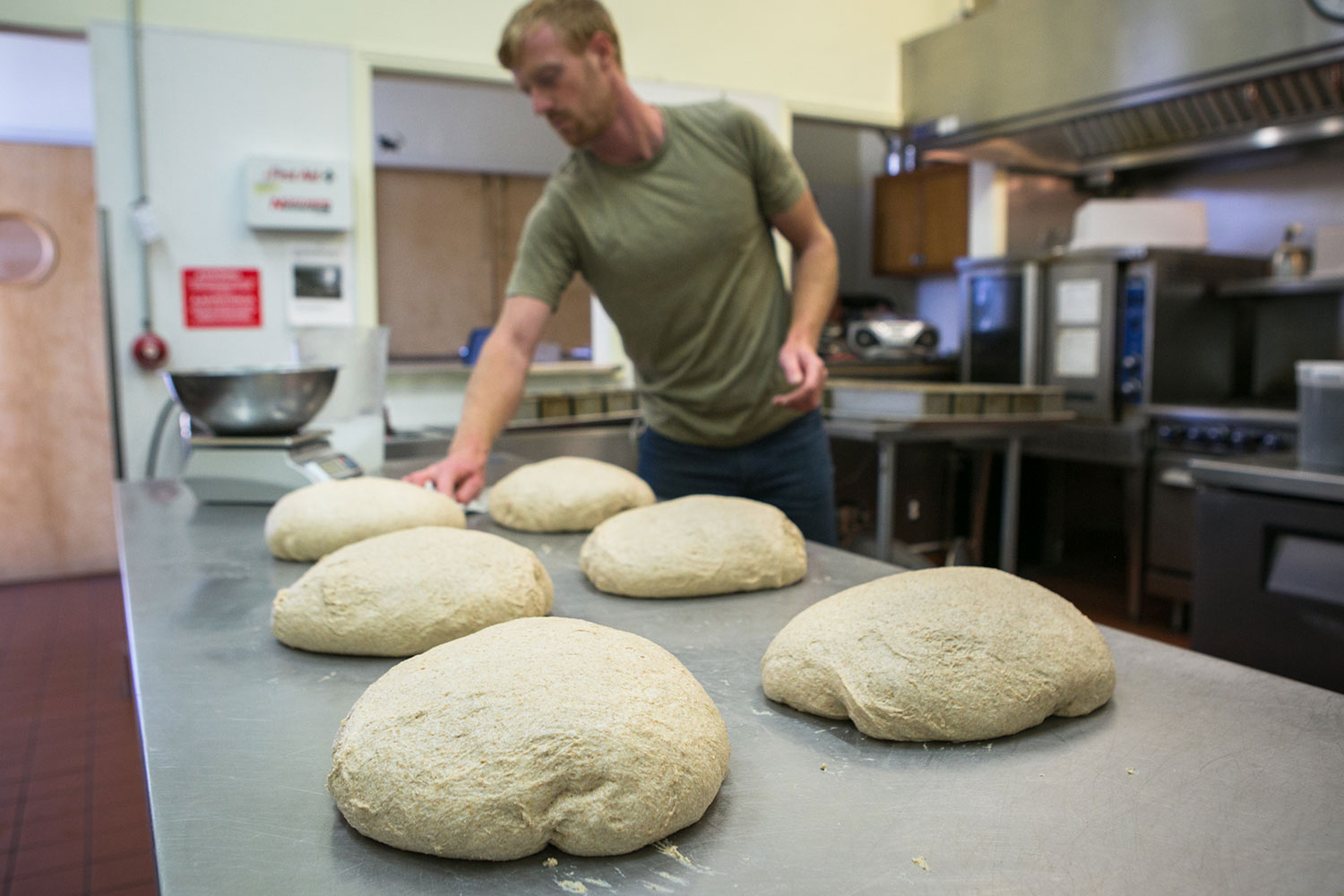 Eliot in the kitchen with loaves of dough ready for the oven