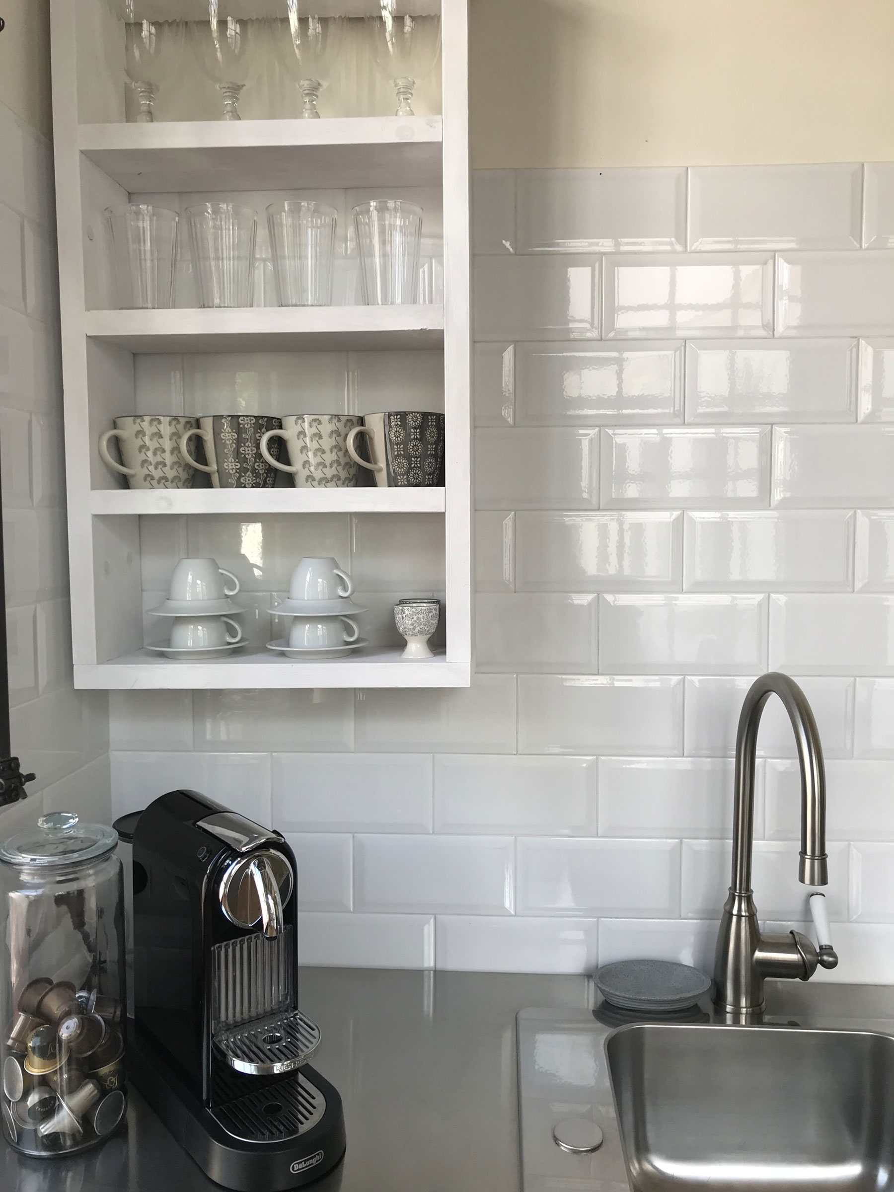 a beautiful kitchen sink with stainless steel counter and white subway tile on the walls