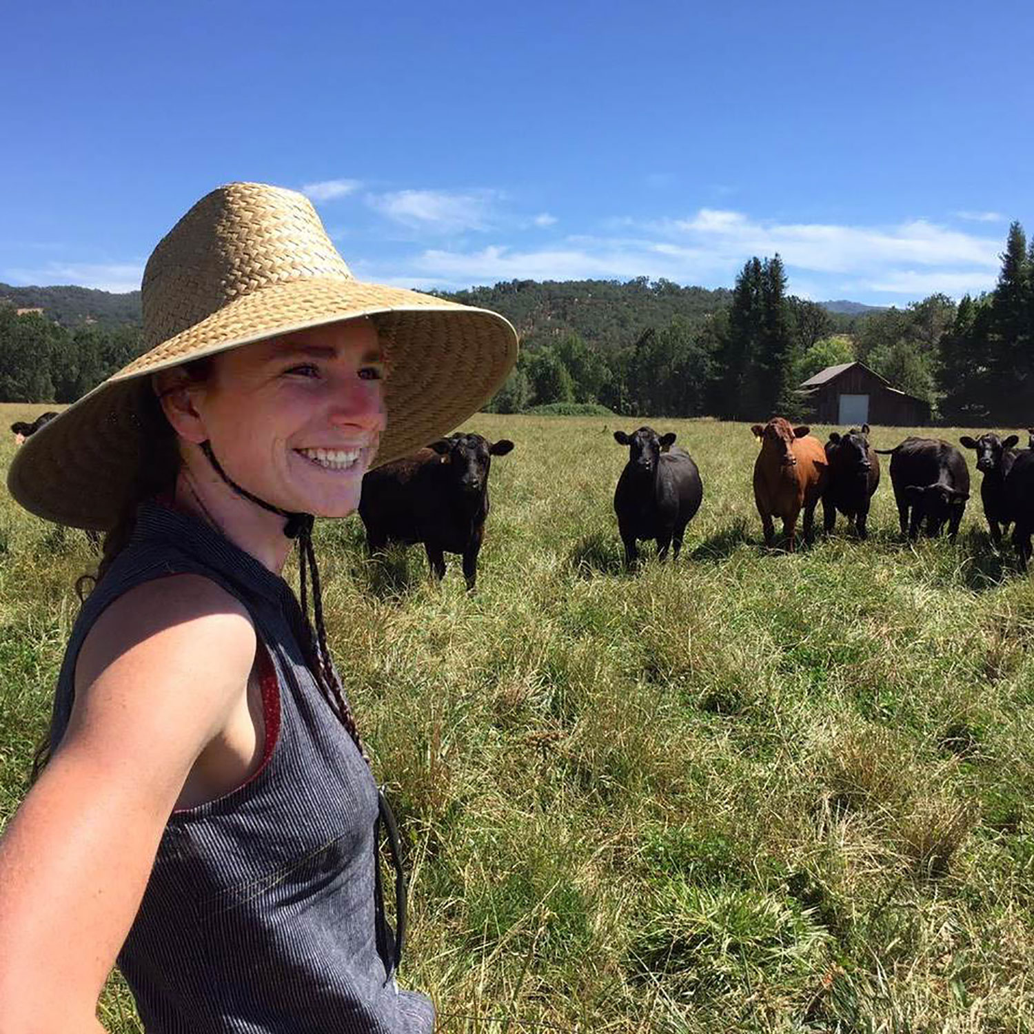 Ruthie King stands in a sunny field with some happy cows