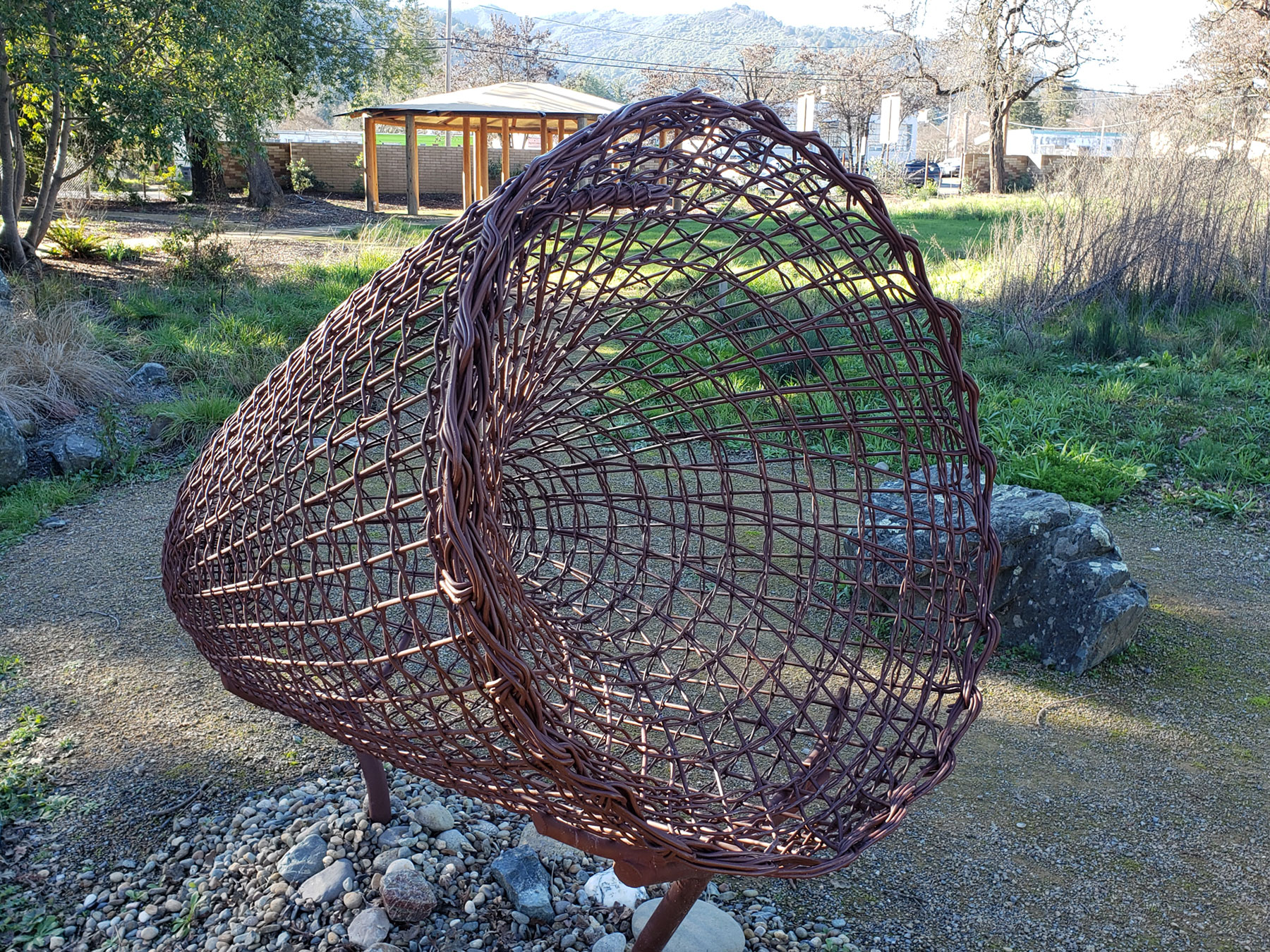 A metal sculpture depicts the design used for a traditional fishing basket. Shoots from the Redbush plant are used in Pomo basket weaving