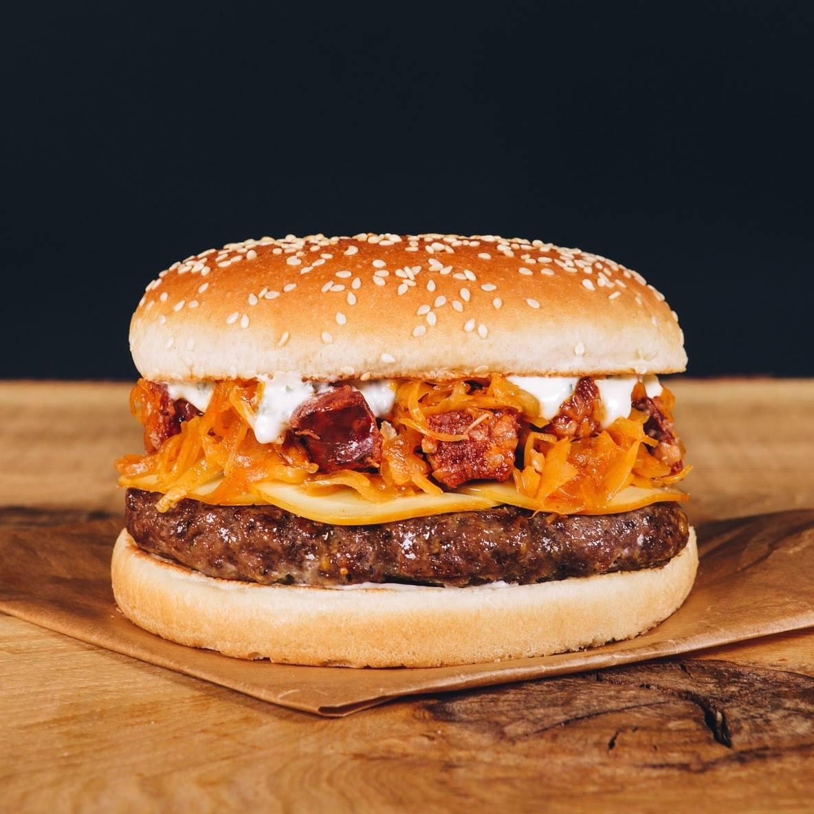 Hovädzí burger s oštiepkom, dusenou kyslou kapustou s klobáskami a bryndzovým dressingom.