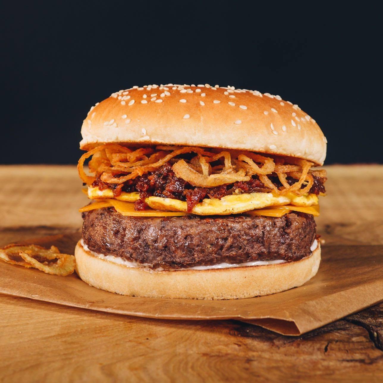 Hovädzí burger s cheddarom, omeletou, slaninovým džemom a chrumkavou cibuľou, podávaný s údenou BBQ omáčkou.