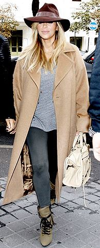 Kim Kardashian wearing her camel coat casually with grey skinny jeans, biker boots and a fab hat to finish off her look