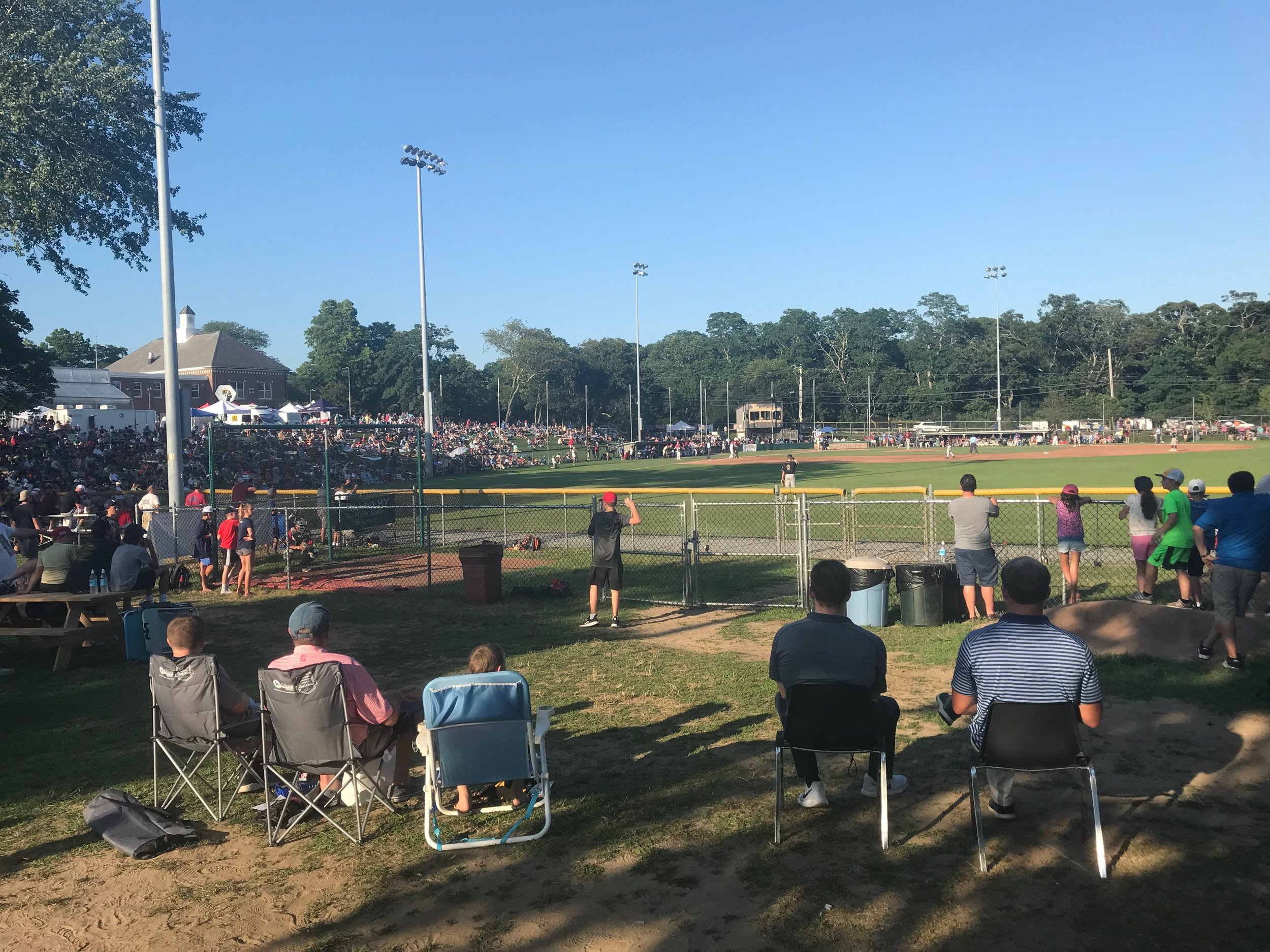 Fans gather on the hill behind the first base side to watch the 2019 Cape League All Star Game.  Photo by Harrison Meyers