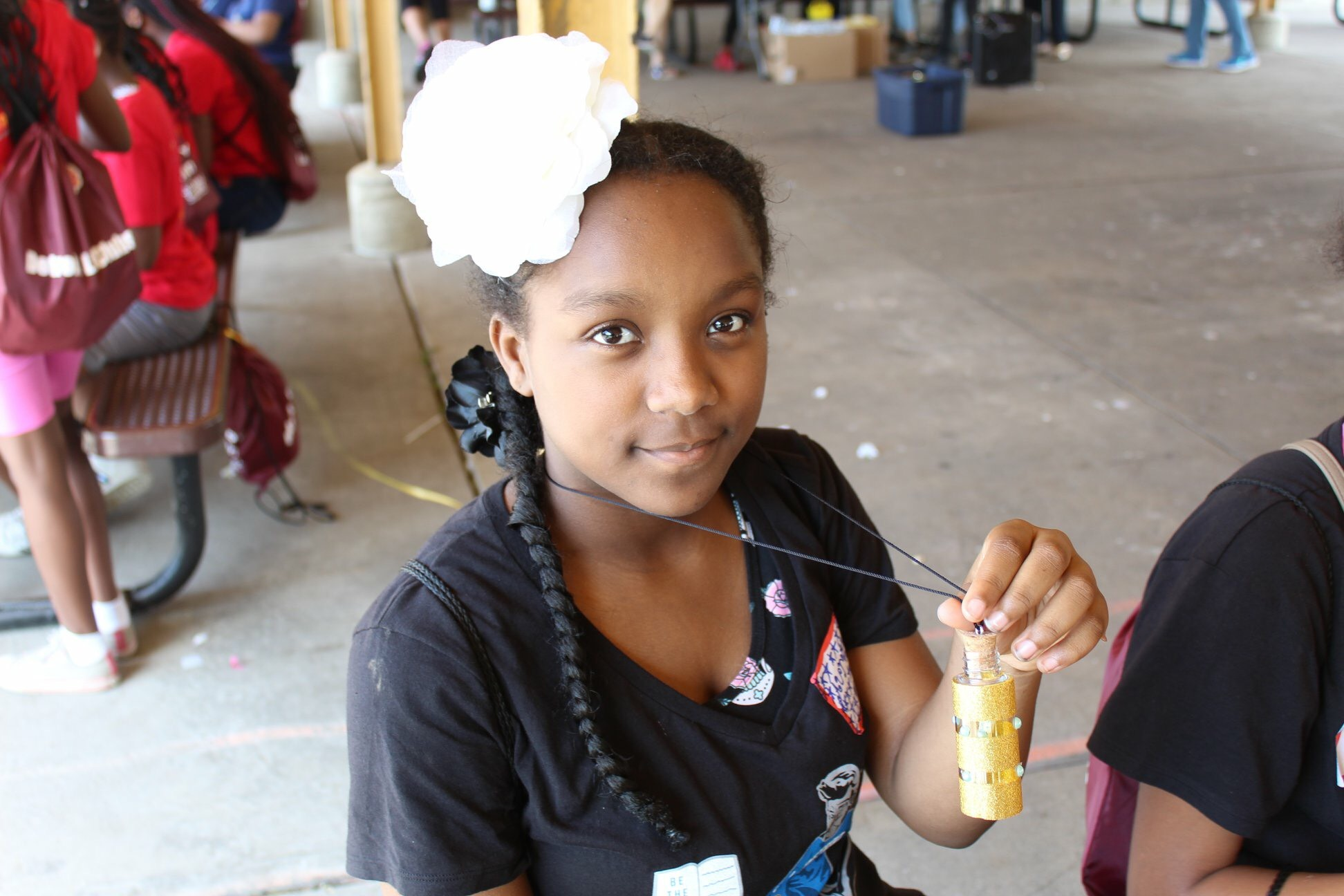 """A LitKid shows off her completed """"Message in a Bottle"""" necklace."""