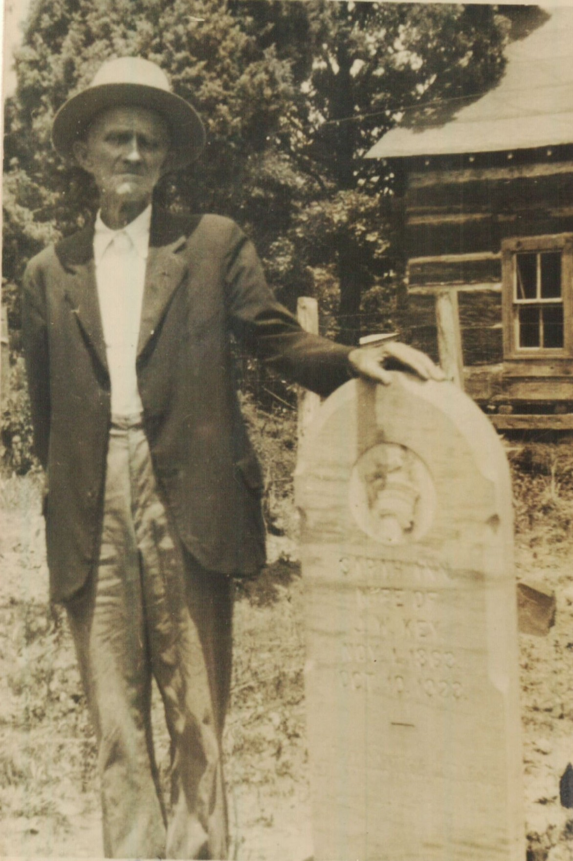 John W. Key poses with his wife's tombstone. Upon john's death, his children erected a new, double stone. However, his youngest son was unable to part with the original stone and it now resides at his home place. I wonder if someone will find it there in years to come and think the grave is there too?