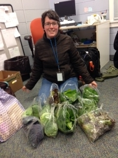 Carina Saavedra, Alliance's former AmeriCorps member, with bags of lettuces and vegetables ready to give to our patients!