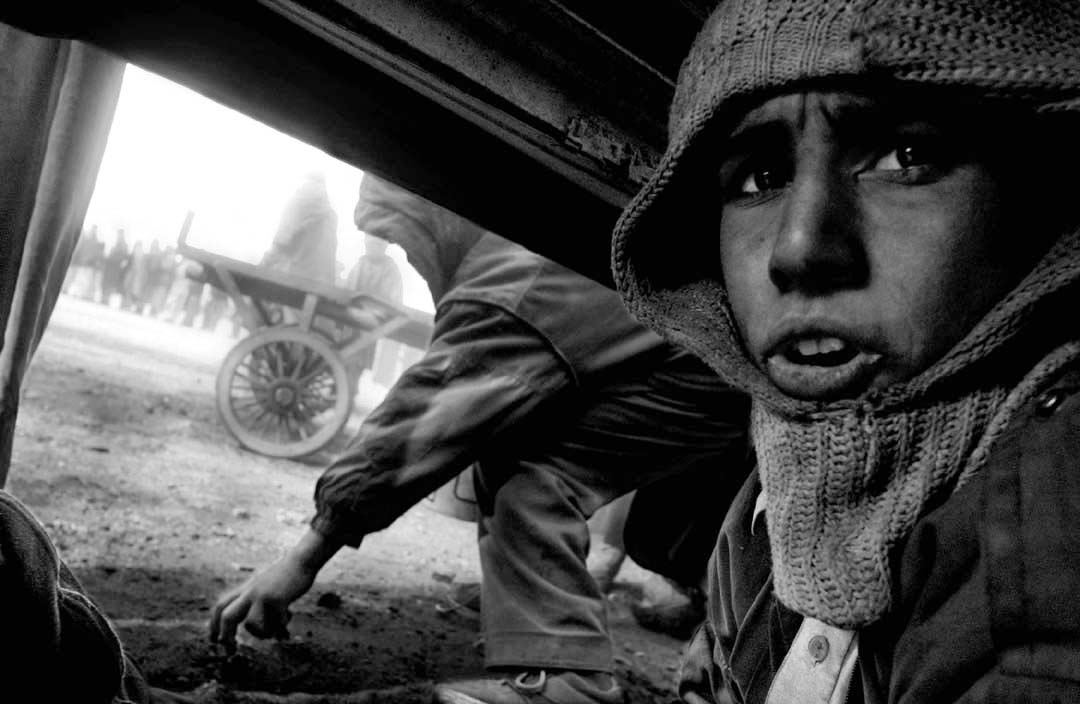Children collect scraps of coal at an aid distribution site. Kabul, Afghanistan 2002