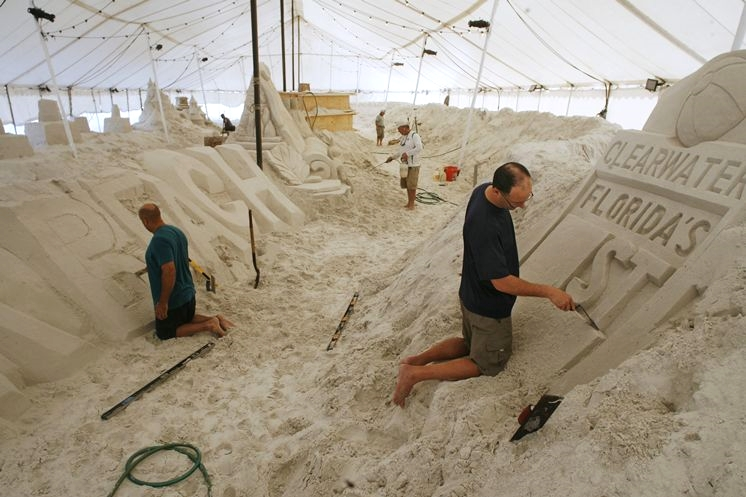 Artists working on their sand sculptures.