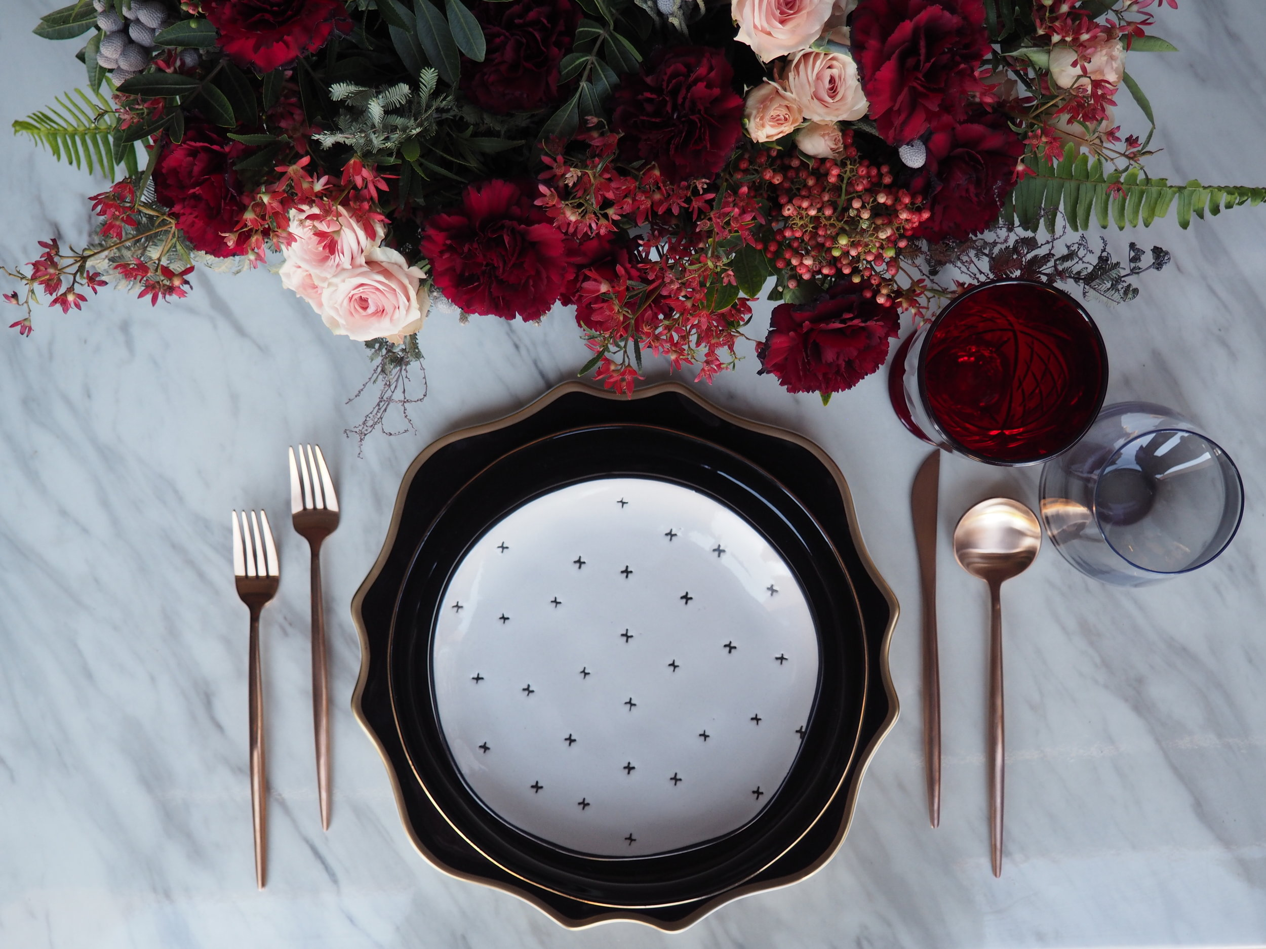 Featuring: Smoke Grey Stemless, Gold Flatware, Scalloped Black & Gold Charger, Aura Black & Gold Dinner Plate