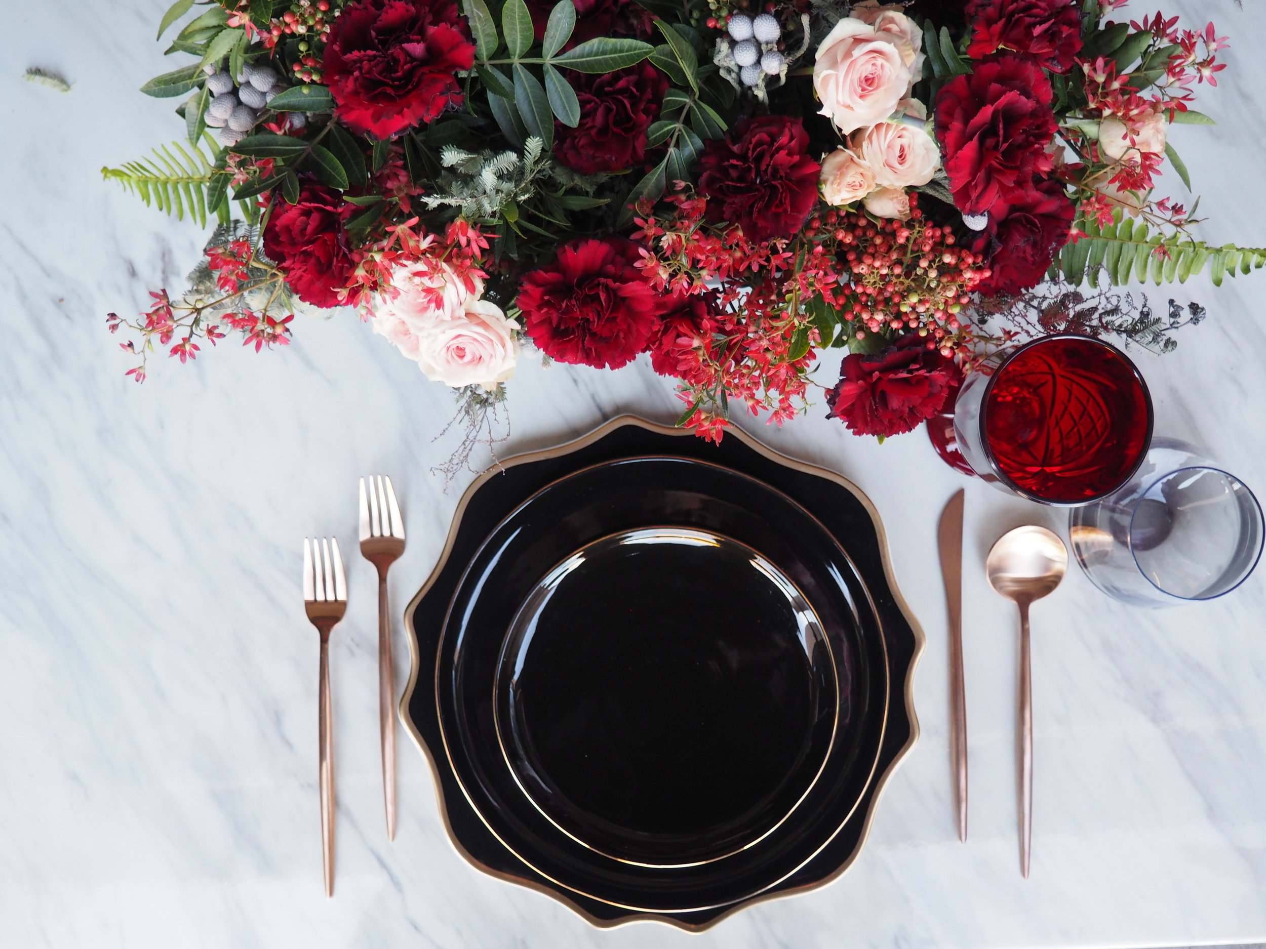 Featuring: Smoke Grey Stemless, Gold Flatware, Scalloped Black & Gold Charger, Aura Black & Gold Dinner Plate & Aura Black & Gold Salad Plate.