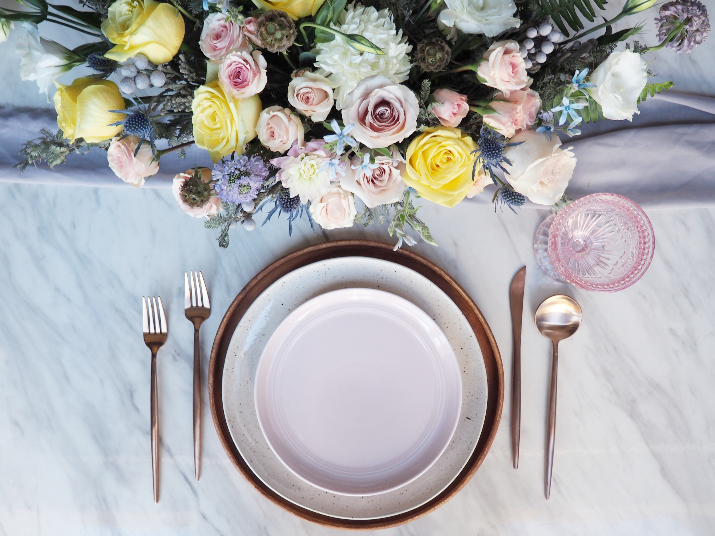 Featuring: Eclectic Pink Goblet, Rose Gold Flatware, Acacia Wood Charger, Speckle Dinner Plate & Blush Salad Plate