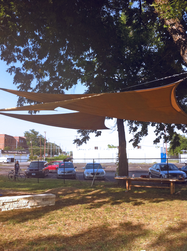 A shade sail canopy, benches, and large table create a gathering space.
