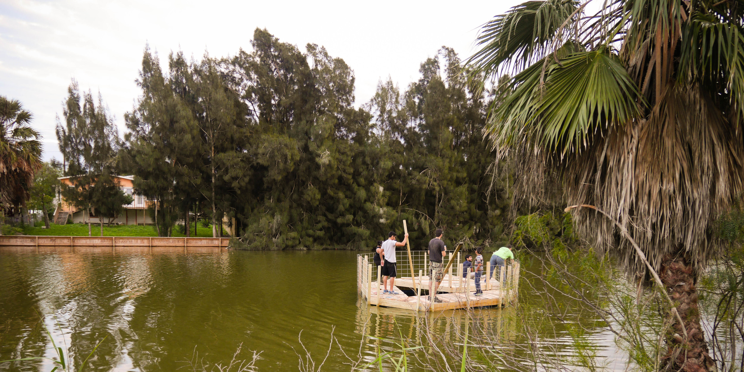 Floating the platform down the Resaca to its final location.