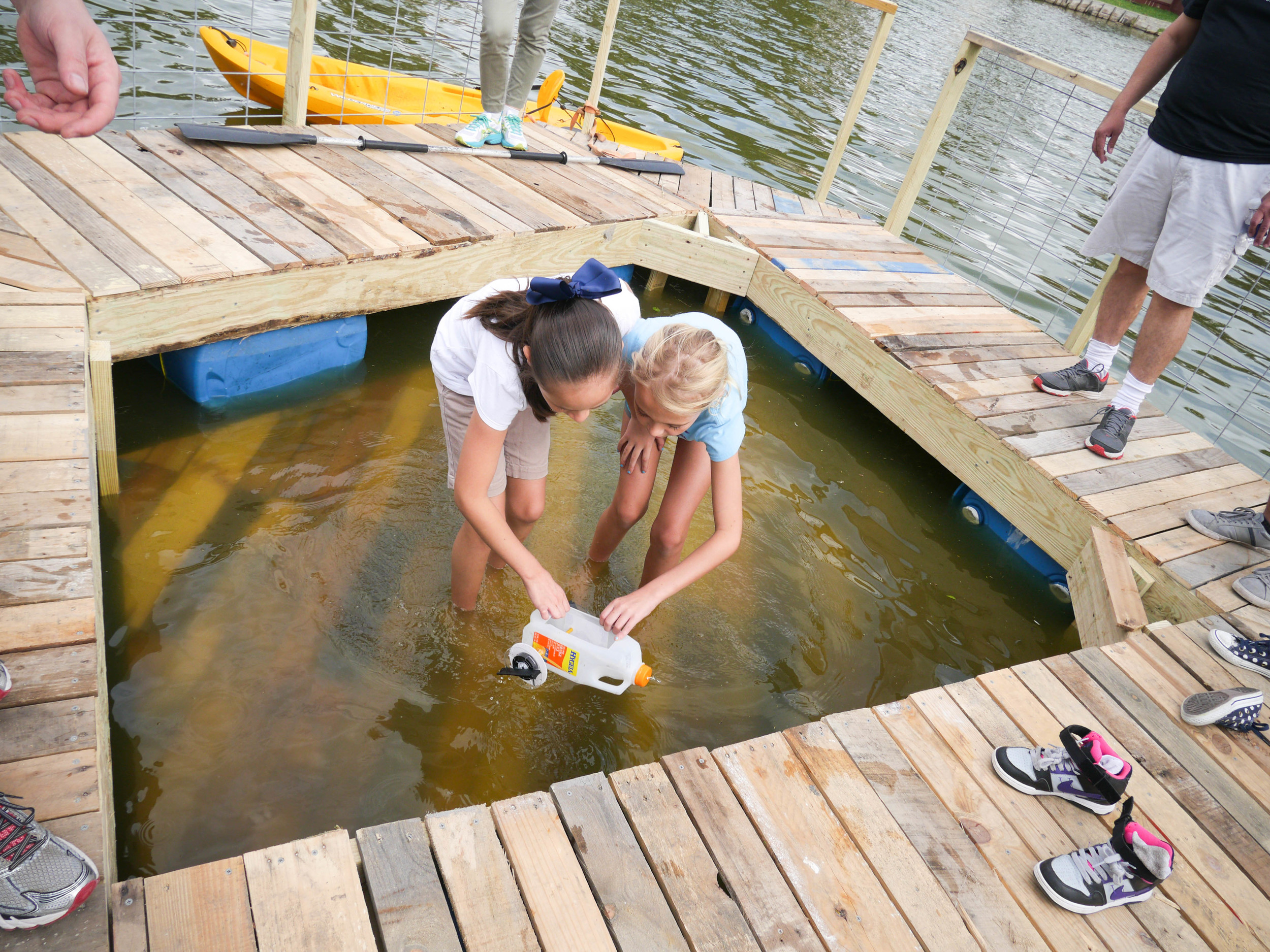 Kids playing with homemade boats.
