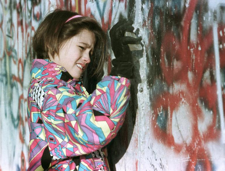 A West German girl hammering at the wall with a stone