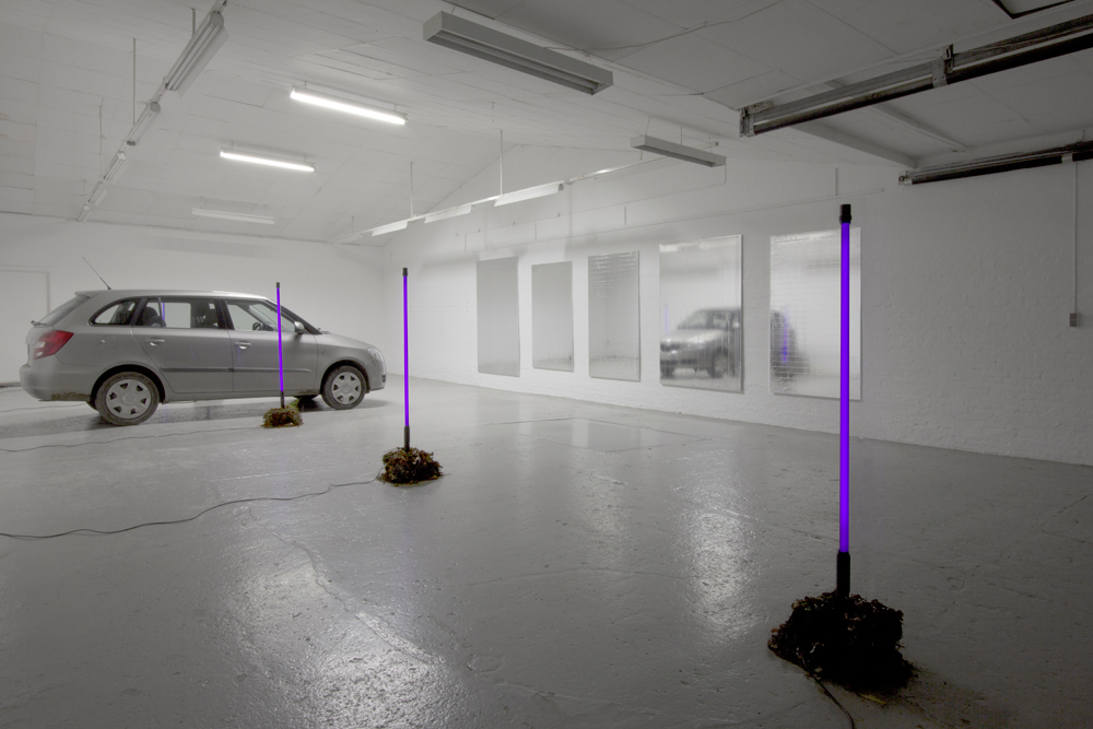 NEW PAINTINGS CAUGHT IN THE HEADLIGHTS OF PARKING CARS, 2012 Mylar emergency blankets (silver), stretchers, outdoor UV light tubes, turf, cars
