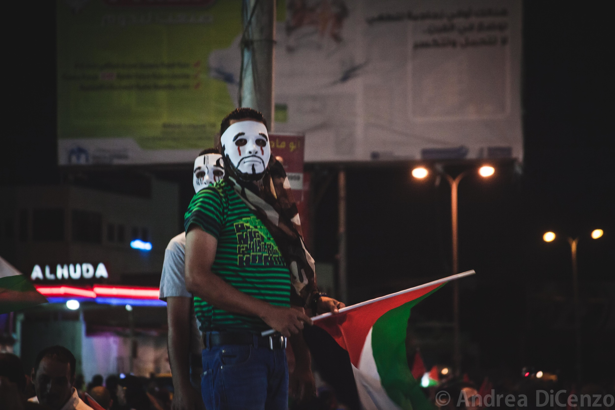 Two protestors survey the crowd in the growingly popular 'V for Vendetta' mask. Concealing your identity can be crucial at these sort of demonstrations forPalestinians participating in protestsfear that the Israeli military will use photos from demonstrations like theseto accuse them of breaking laws.