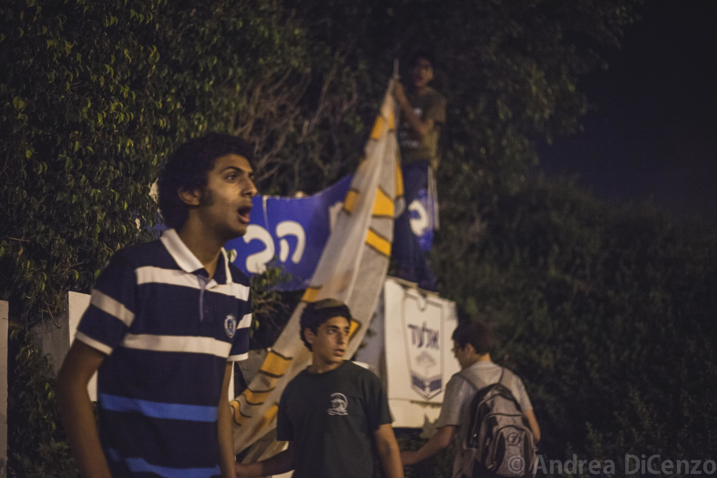 A group of boys from the Israeli settlement of El Adcautiously addressesstrangers passing by as they try to erect a large homemade banner on the evening the bodies of the three missing Israeli teenagers were discovered.