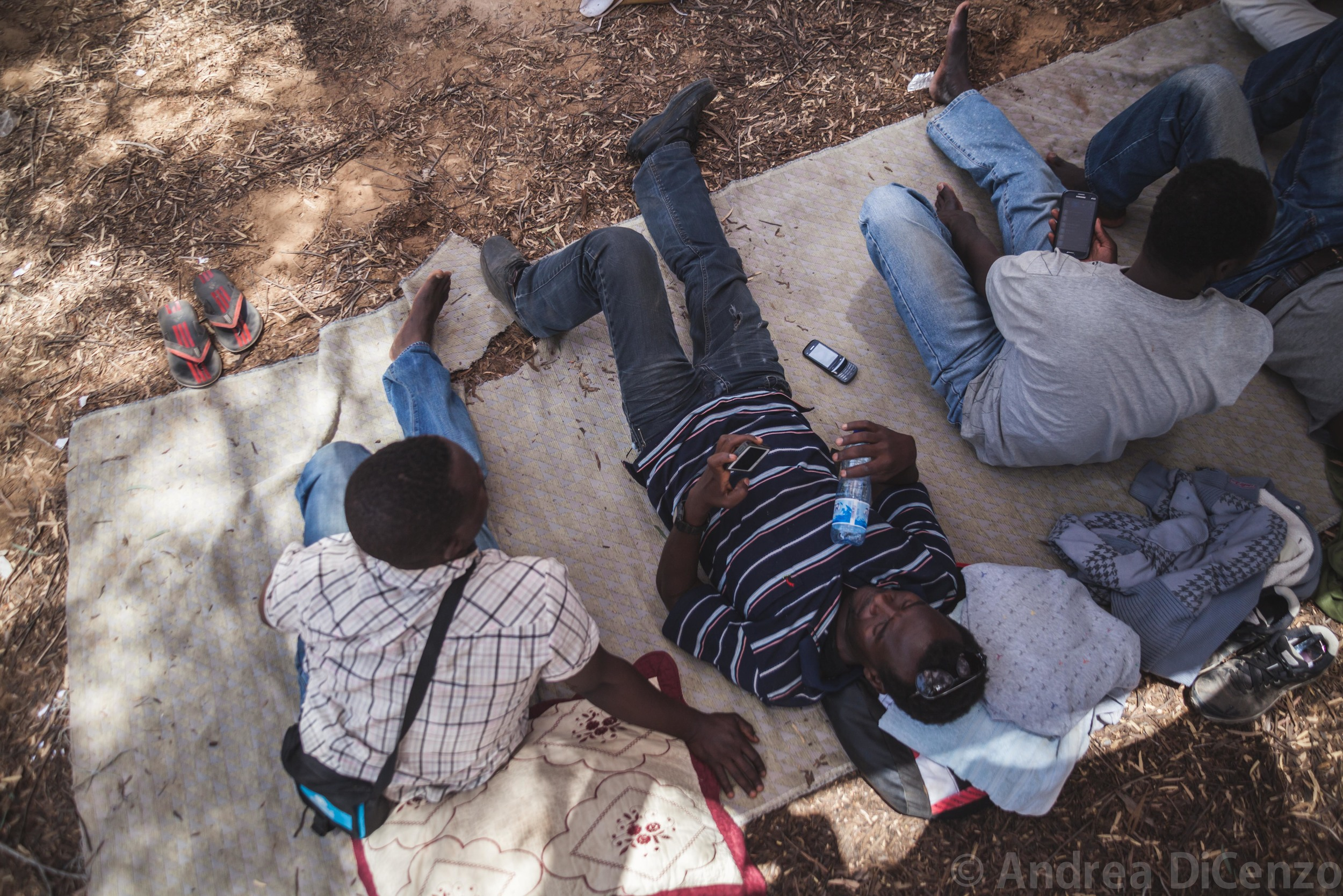 Three men rest under the shape of small trees as they protest the living conditions in Holot Detention Center.