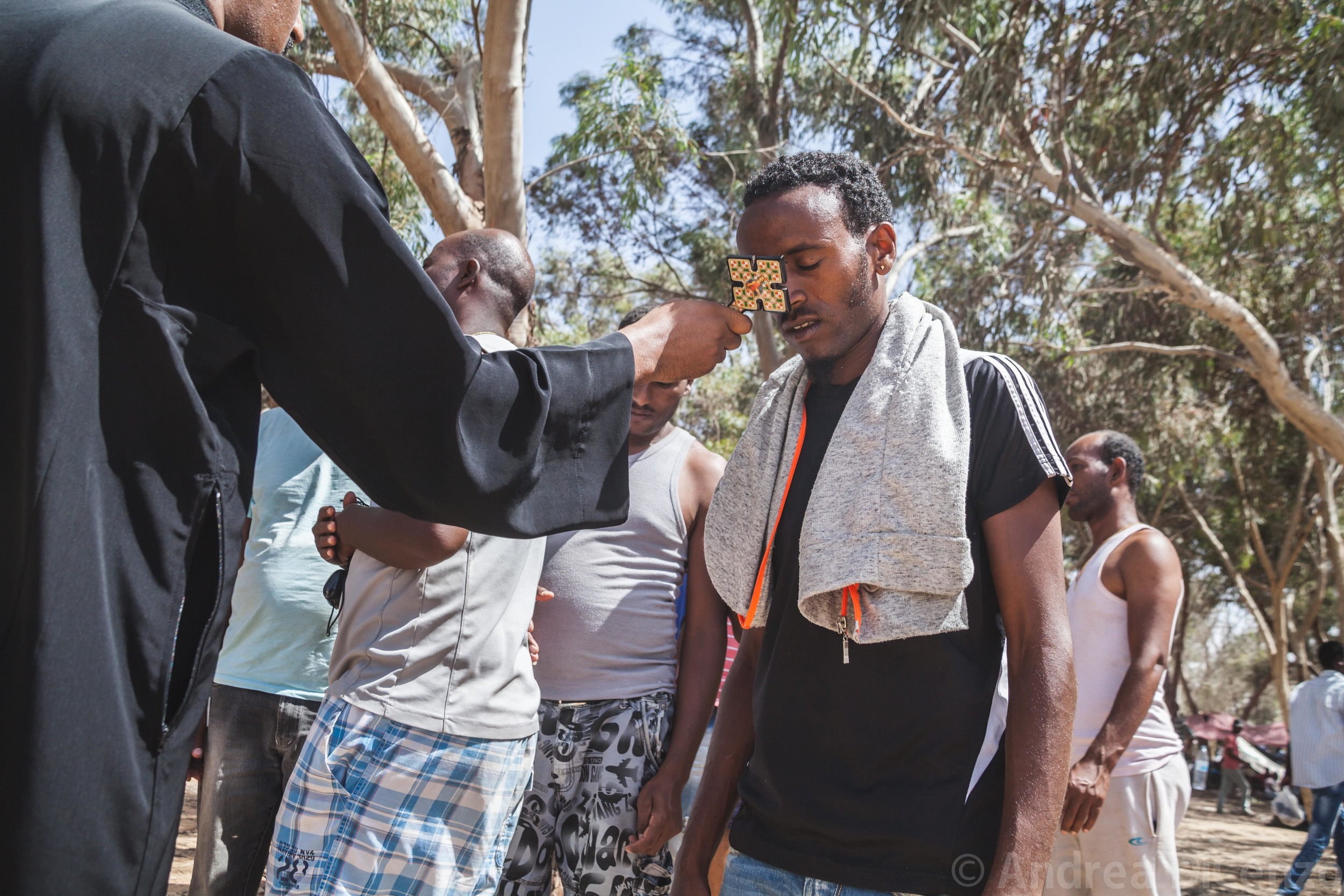 An Eritrean christian receives a blessing from a leader of the Christian community. The gentlemen is part of a protest from asylum seekers in Holot Detention Center who have left the establishment to protest living conditions for them in Israel.