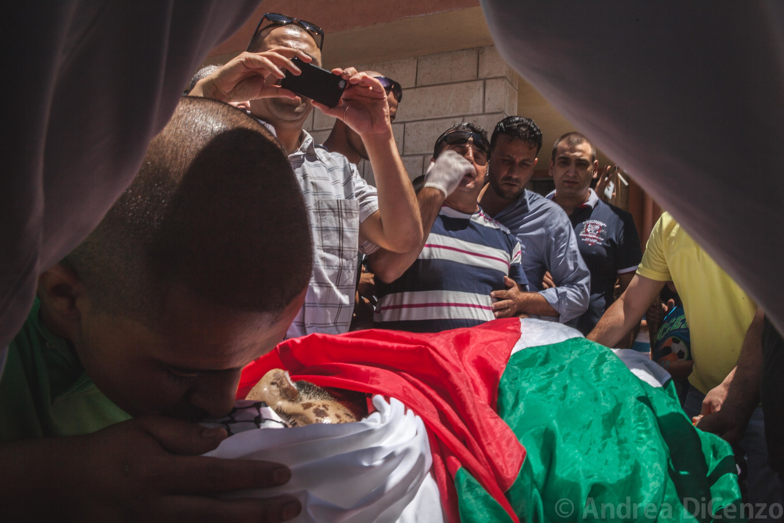 A stranger kisses the body of Mohammed during a funeral precession in East Jerusalem.Doctors and staff perform a traditional funeral outside Al-Makassed hospital for the funeral of theyoung man from Gaza. He arrived at 3am earlier in the day but didn't make it through the night.