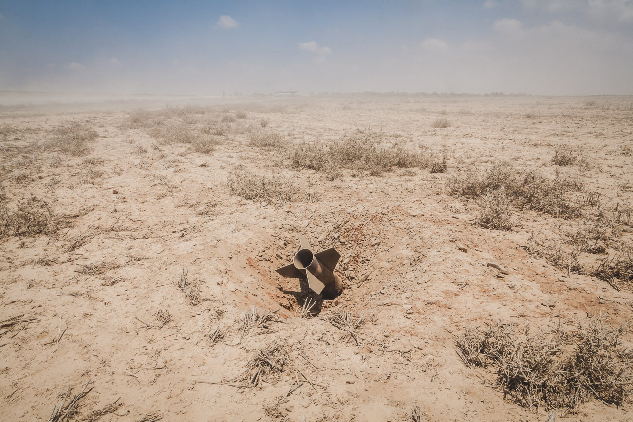 A rocket sticks out of the ground in a fieldthat surrounds kibbutzNirim - located only two kilometers from the south eastern Gaza border.