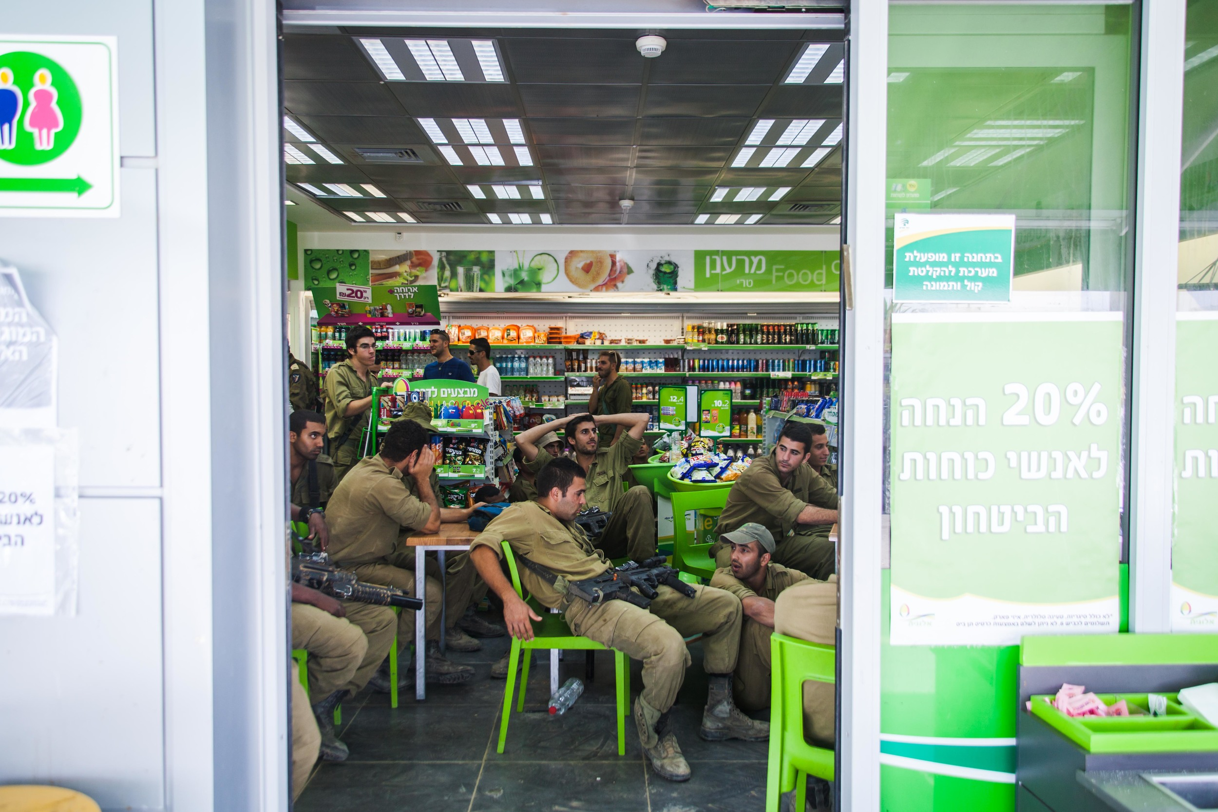 Soldiers watch the news and eat ice-cream in a gas station close to their base on the border of Gaza/Israel.