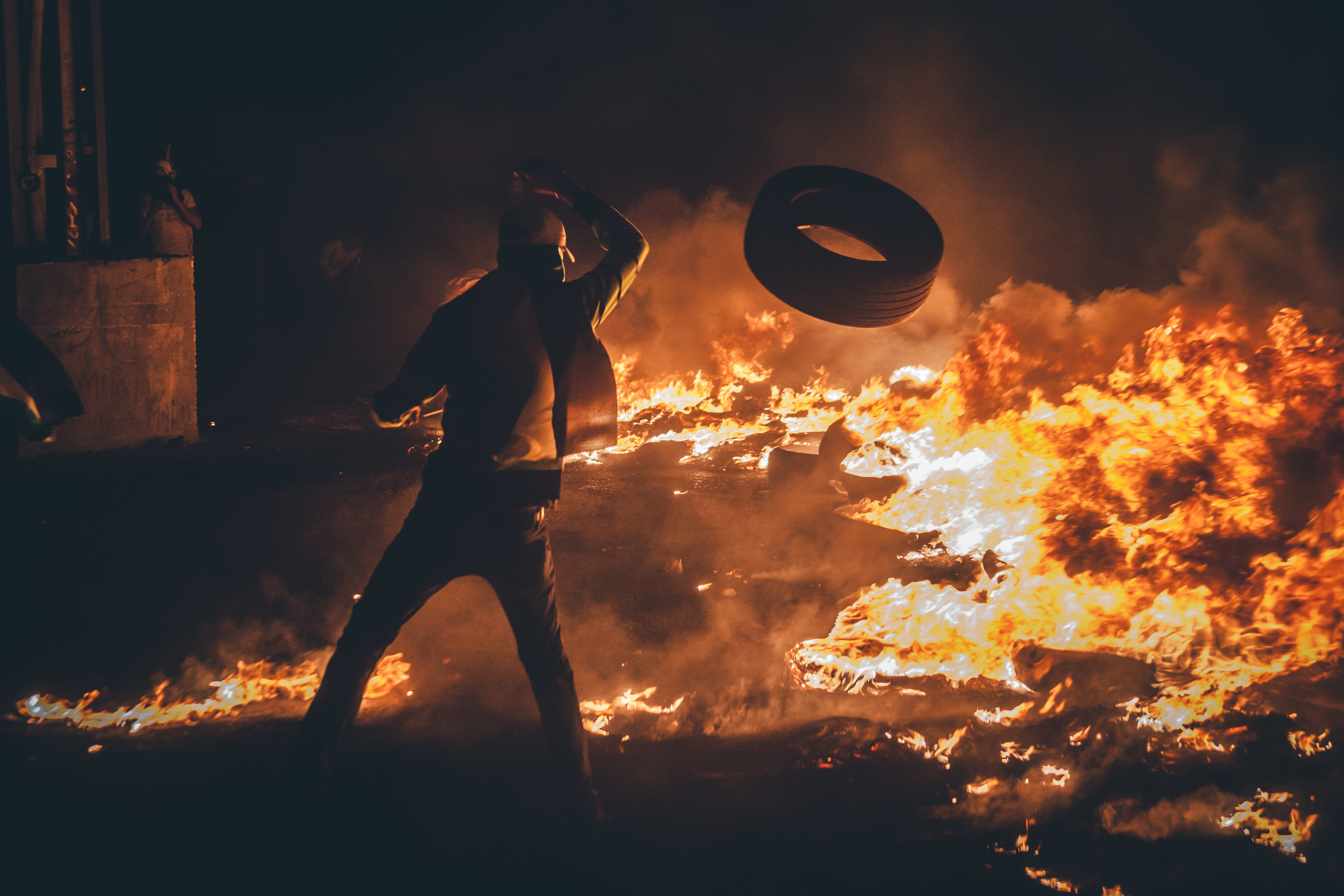 A Palestinian protestor throws a tire onto the flames. The smoke from the fire often creates a smoke screen between the protestors and the IDF, leaving visibility between the two side at times nonexistent.