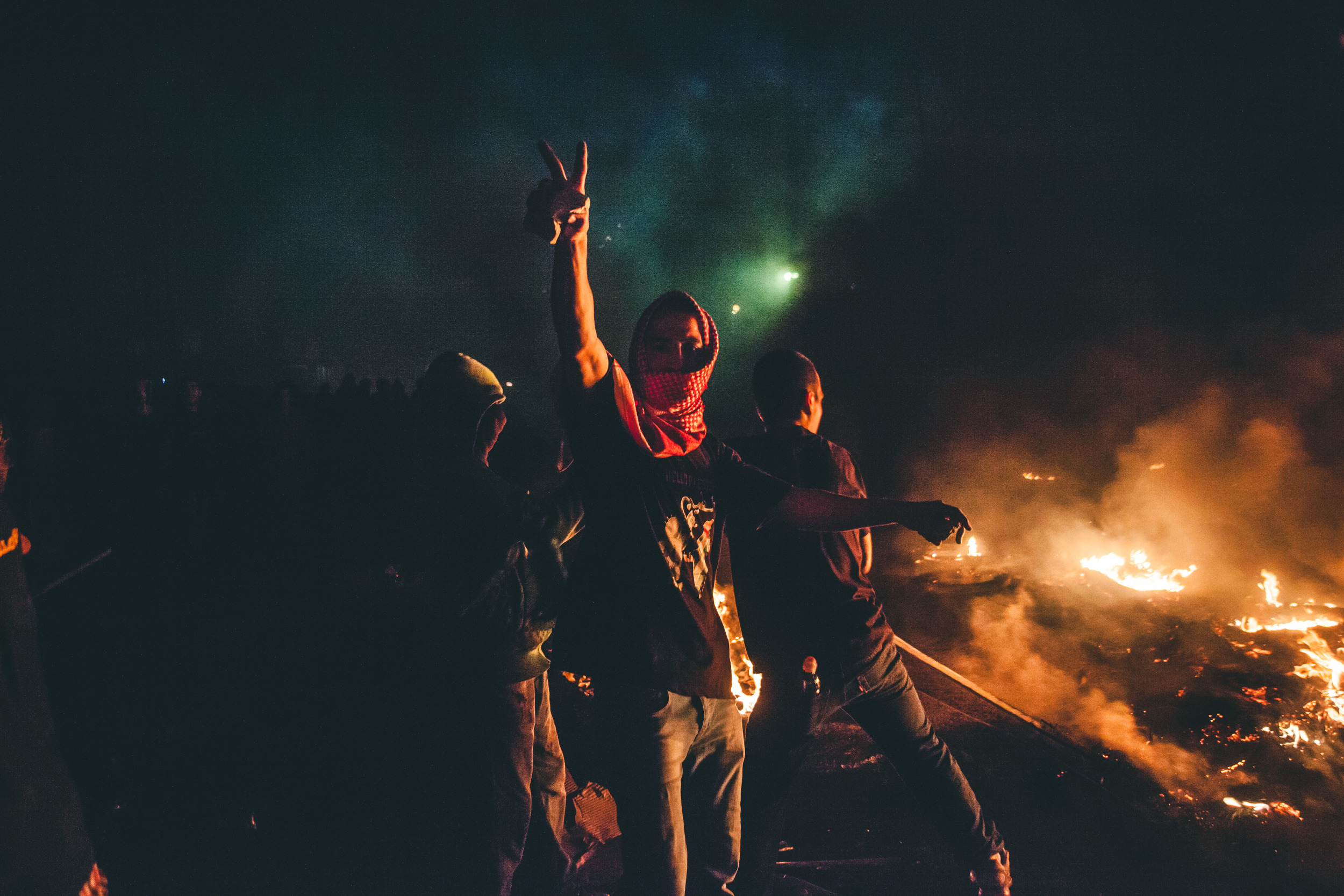A keffiyeh clad demonstrator holds up a peace sign while clutching a rockat Qalandia checkpointas the fire and protest roars behind himduring thelargest protest of the summer in the West Bank- the48Thousand March.23rd July, 2014.