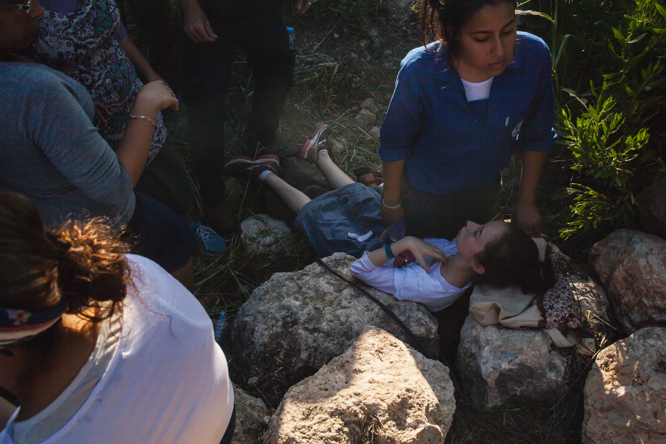 A child faints from the overbearing heat and dense crowdduring the state funeral for the three murdered Israeli teenagers. 1 July 2014.