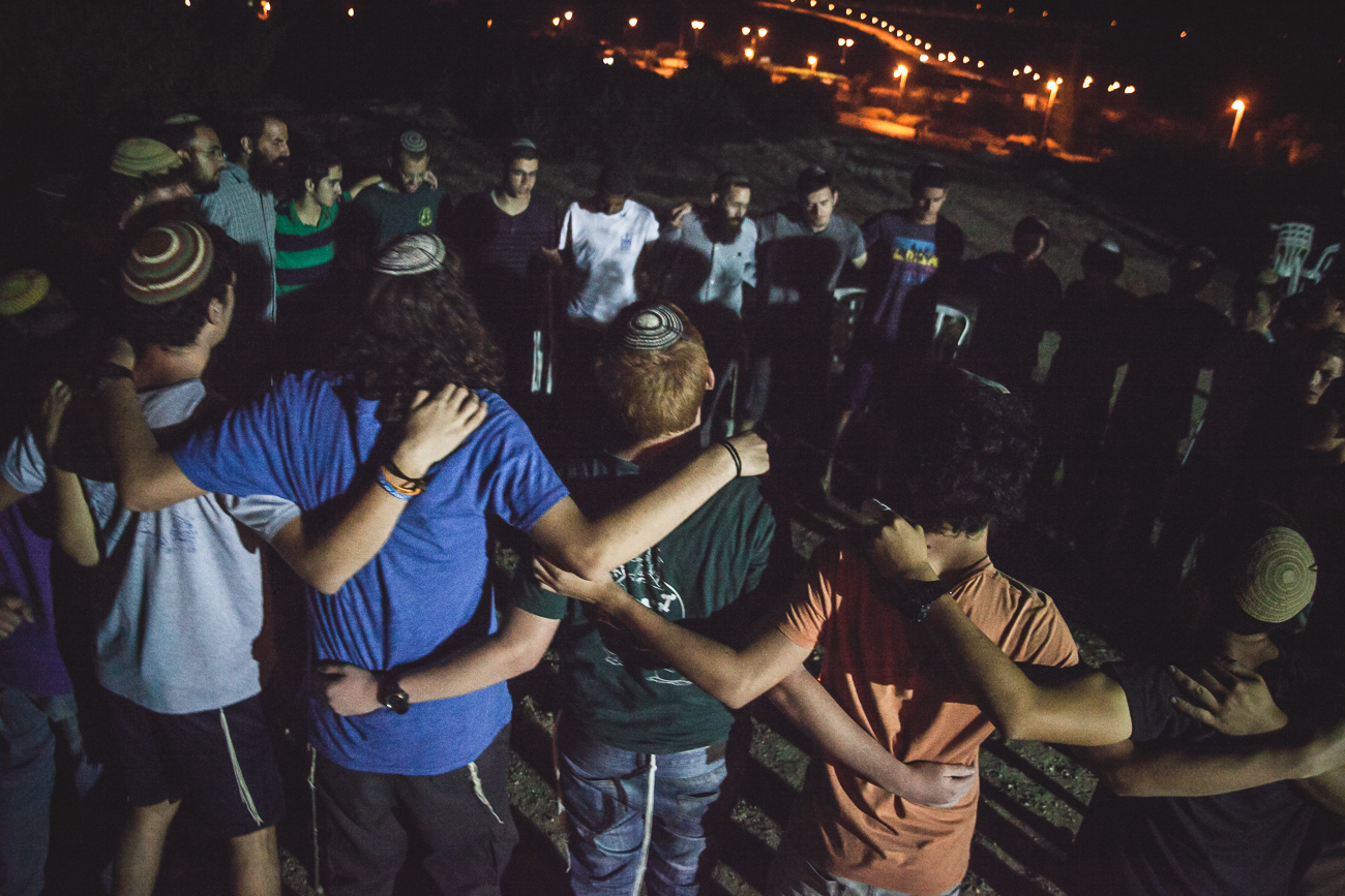 Community members of Nof Ayalon - home to 17-year-old Naftali Frankel - gather to mourn in the early hours of the morning after receiving news that Naftali, and his two friends, were discovered dead. 30 June 2014.