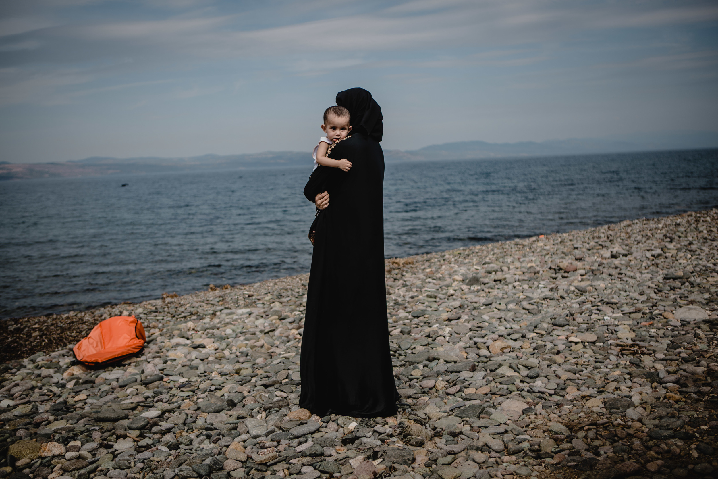 A women holds her child while looking back towards the sea she and her family just crossed from Turkey.