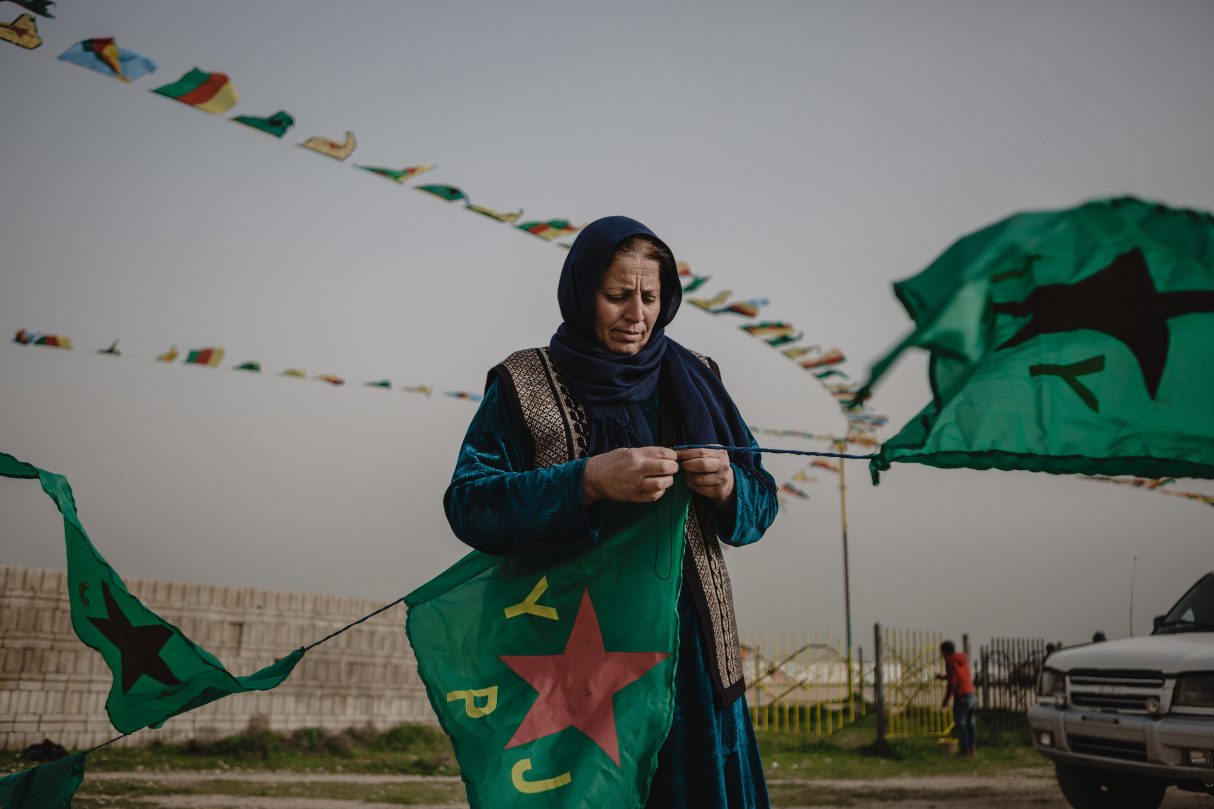 A women sews Kurdish People's Defence Units (YPG) flags in Amude, Syria. The flags are for Newroz celebration that are being organized by the Democratic Union Party (PYD).