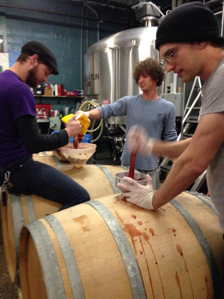Smooshing Michigan cherries into a barrel of lambic. Photo from Upland Brewing Co.