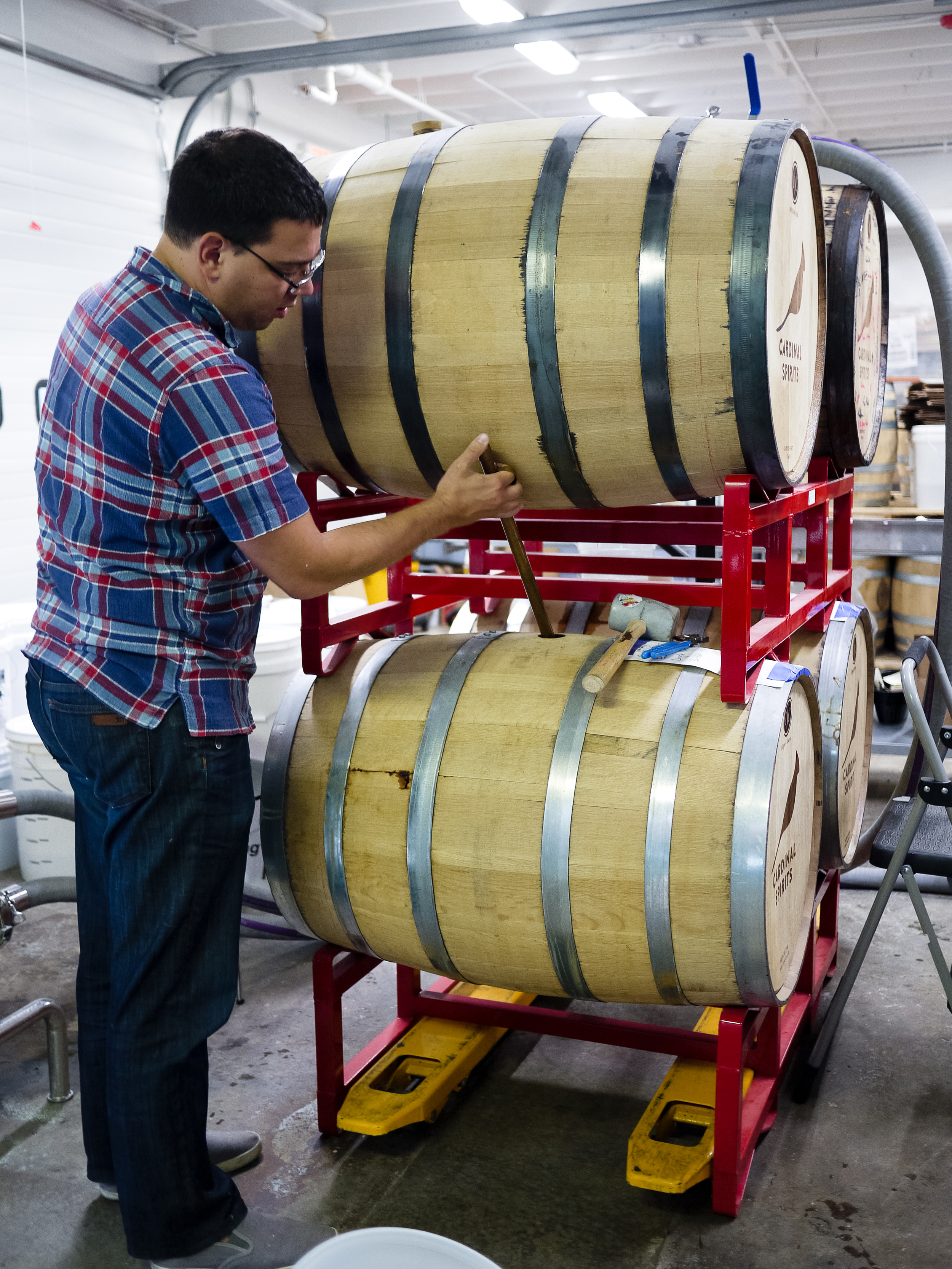 That's Cardinal co-founder Jeff Wuslich checking on the contents of the barrels using a whiskey thief, a tool that pulls out a small sample.