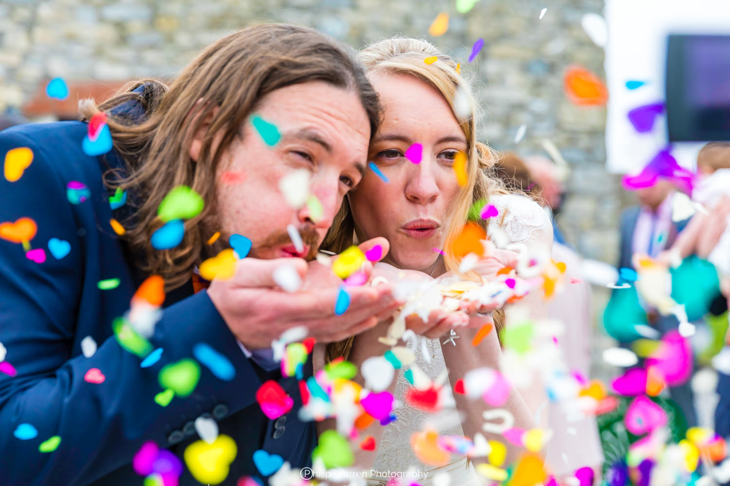 bride and groom blowing brightly coloured confetti