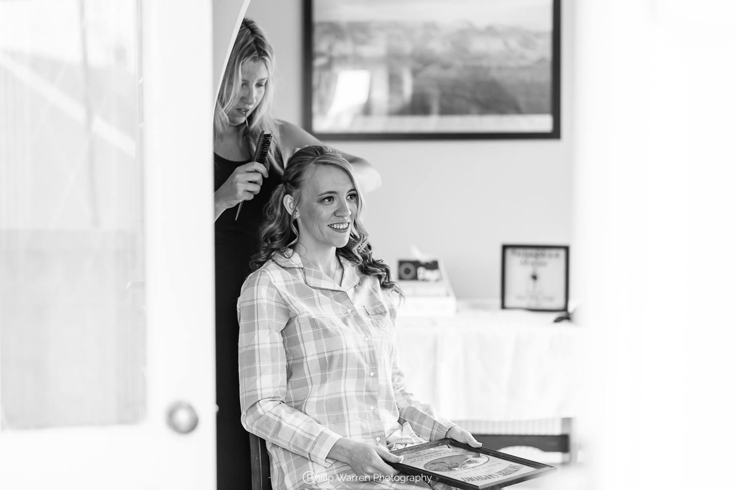 bride having hair done before wedding at home