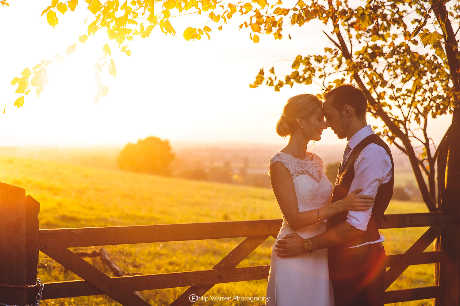 bride and groom holding each other in the sunset
